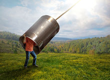 Listening with a tin can. A man listens to the sounds from above with a tin can Royalty Free Stock Photos