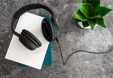 Listening to audio books concept with headphones on stack of books on stone background royalty free stock photo