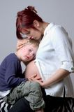 Listening to the baby. Pregnant mother (9th month)with her son royalty free stock images