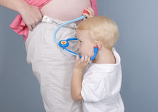 Listening to baby heartbeat. Son listening his mother stomach Royalty Free Stock Photos