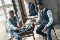 Listening to client requirements. Young fashionable designer choosing fabric with his client while sitting in the workshop stock image
