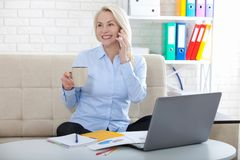 Listening to clients requirements. Beautiful middle aged woman with glasses talking on smart phone and smiling at her. Working place with documents.siting in stock image
