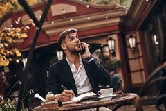 Listening to clients requirements. Handsome young man in smart casual wear talking on his smart phone and writing something down while sitting in restaurant royalty free stock photos