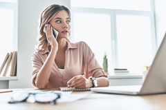 Listening to clients requirements. Beautiful young woman in smart casual wear writing something down and talking on the phone while sitting in modern office royalty free stock images