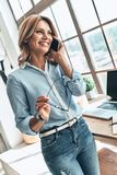 Listening to clients requirements. Beautiful young woman talking on the phone and smiling while standing in the creative office royalty free stock image