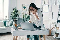 Listening to clients requirements. Beautiful young woman using laptop and talking on the phone while working in home office stock image