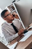 Listening to clients requirements. Serious young man in formalwear talking on the phone while sitting in the office royalty free stock photos