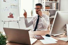 Listening to clients requirements. Serious young man in formalwear talking on the phone and gesturing while sitting in the office royalty free stock images