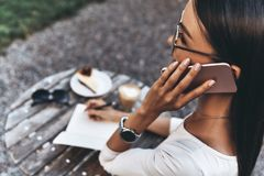 Listening to clients requirements. Rear view of attractive young woman talking on a smart phone and writing something down while sitting in restaurant outdoors stock photo