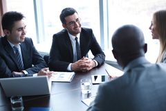 Listening to colleague. Image of business people interacting at meeting Stock Image