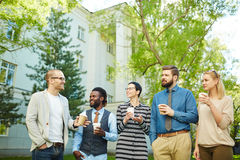 Listening to explanation of colleague. Young co-workers looking at happy employee explaining his view point at outdoor meeting royalty free stock photo