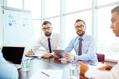 Listening to explanation. Contemporary employees discussing new ideas and plans royalty free stock image