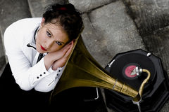 Listening to gramophone. Young attractive woman dressed in forties style listening to gramophone Royalty Free Stock Image