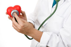 Listening to the heart. Hands of Dr. listening with a stethoscope a heart Royalty Free Stock Photo