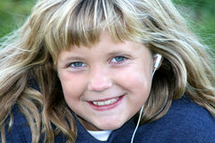 Listening to Her Ipod. A pretty young blond 8-year old girl listens to music on her Ipod Royalty Free Stock Images