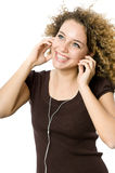 Listening to an MP3 player. A beautiful young girl listening to music on her mp3 player Royalty Free Stock Photo