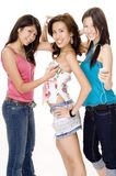 Listening to music #1. Three pretty young asian women listen to music on portable music devices Royalty Free Stock Photo