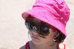 Listening to music. A young girl relaxed at the beach listening to music with earphones in her ears and wearing a hat to protect herself from the damage of the Royalty Free Stock Photo