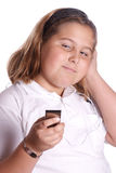 Listening To Music. A young girl listening to her MP3 player isolated against a white background Royalty Free Stock Photo