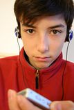Listening to music. Teen with headphones and mp3 royalty free stock photo