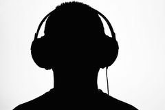 Listening to music. A silhouette of a male head listening to music against a white background Stock Photos
