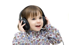 Listening to music. Little girl listening to music with headphones on white background Royalty Free Stock Photos