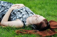 Listening to music. Pensive young woman lying on grass listening to music outdoors Royalty Free Stock Photos