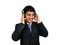 Listening to music. Young Indian business man listening to music (Series Royalty Free Stock Photo