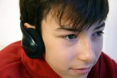 Listening to music. Teen with headphones stock photo