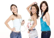 Listening To Music #4. Three attractive young asian women listening to music on portable mp3 players Royalty Free Stock Photos