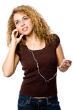 Listening To Music. A young woman listening to music on a portable mp3 player royalty free stock image