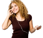Listening To Music. A young woman listening to music on a portable mp3 player royalty free stock photography