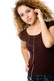 Listening To Music. A young woman listening to music on a portable mp3 player stock images