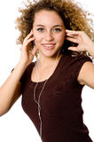 Listening To Music. A young woman listening to music on a portable mp3 player stock photos
