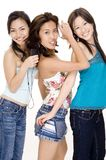 Listening to Music #5. Three attractive young women listening to music on their mp3 players Royalty Free Stock Images
