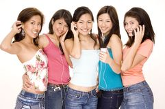 Listening To Music #7. Five attractive asian women with gadgets (phones and mp3 players Stock Photo