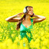 Listening to music in flowers. Young woman with headphones listening to music in yellow flowering field Royalty Free Stock Image