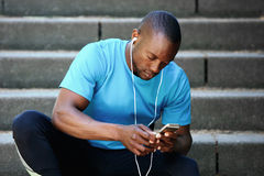 Listening to music and looking at mobile phone Stock Photos