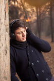 Listening to music outside. Young man listening to music on the headphones next to a tree Stock Photo