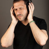 Listening to music with pleasure. Middle age man with closed eyes, listening to music over dark background. Square format Stock Photography