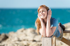 Listening to music at the sea Royalty Free Stock Image