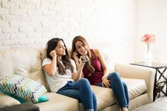 Listening to music and singing. Cute pair of friends relaxing at home and listening to some music together Stock Photo