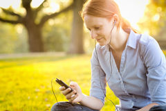 Listening to Music on a Smartphone at Sunset Royalty Free Stock Photos
