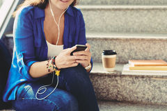 Listening to music. Smiling woman in earphones listening to music on her smartphone Stock Photos