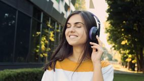 Listening to the Music. Smiling woman enjoying listening to the music while walking before modern building stock footage