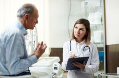 Listening to patient. Senior patient explaining his problem to doctor during appointment Royalty Free Stock Photo