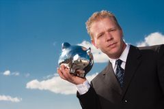 Listening to piggy bank Stock Image