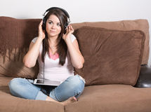 Listening to something on tablet using large headphones Stock Photos