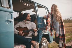 Listening to the song of love. Handsome young men playing guitar for his beautiful girlfriend while sitting in blue retro style mini van Royalty Free Stock Images