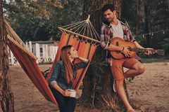 Listening to the song of love. Handsome young men playing guitar for his beautiful girlfriend while spending carefree time outdoors royalty free stock photos